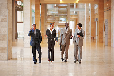 Buy stock photo A successful group of business people walking together
