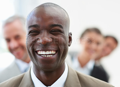 Buy stock photo Portrait of a young African American business man with his business colleagues at his back
