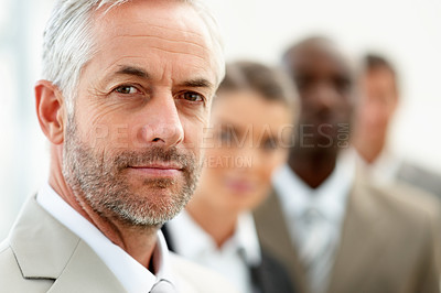 Buy stock photo Closeup of a senior old business man with his colleagues standing in a line behind him