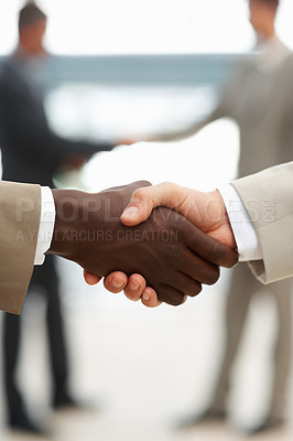 Buy stock photo Closeup of a multiracial handshake between two business men