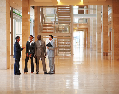 Buy stock photo Group of successful business colleagues standing at a hallway