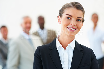 Buy stock photo Portrait of a young business woman with colleagues at the background