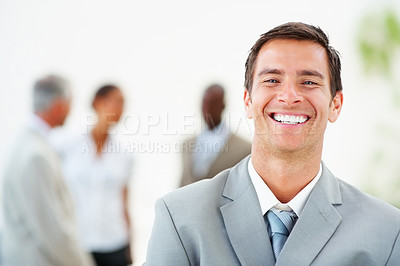 Buy stock photo Portrait of a young business man laughing, with colleagues at the background