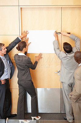 Buy stock photo Group of business colleagues putting up a white sheet on their office wall