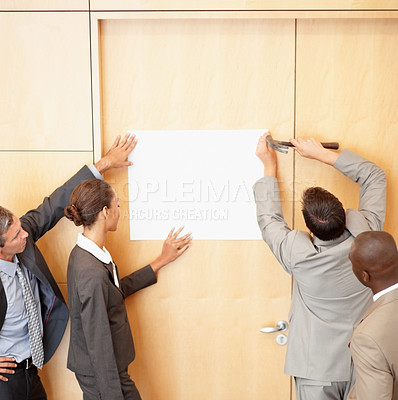 Buy stock photo Rear view of business people putting up a white sheet on their office wall
