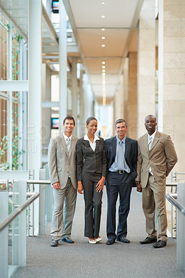 Buy stock photo Portrait of a business team standing together at a hallway