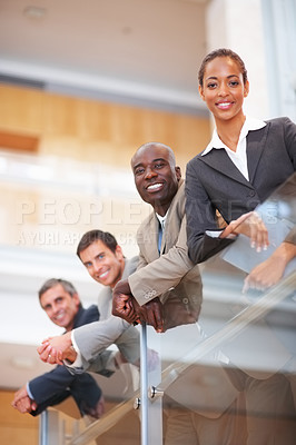 Buy stock photo Portrait of successful business colleagues resting on a glass railing