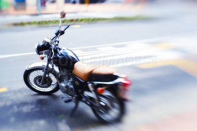 Buy stock photo Shot of a motorbike parked on the side of a road