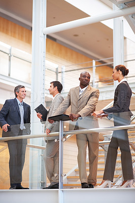 Buy stock photo Portrait of a business group standing by a glass railing