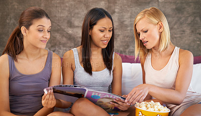 Buy stock photo Shot of a group of riends browsing through magazines while hanging out