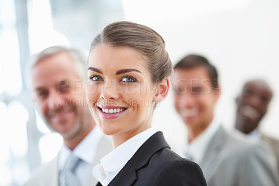 Buy stock photo Blur image of a cheerful business woman in front with her staff standing behind