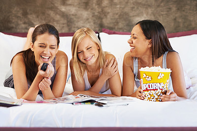 Buy stock photo Shot of a group of friends laughing while watching movies together at home