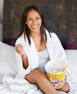 Buy stock photo Portrait of a young woman sitting on her bed with a bowl of popcorn