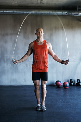 Buy stock photo Shot of a man training with a skipping rope at the gym