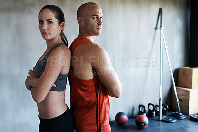 Buy stock photo Cropped shot of a young man and woman in gymwear standing back to back