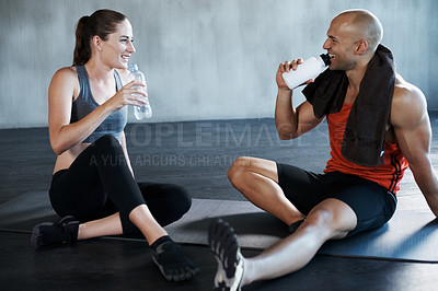 Buy stock photo Shot of a man and woman taking a break after a workout at the gym