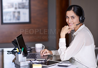 Buy stock photo Shot of an attractive young businesswoman working on a laptop while wearing a headset