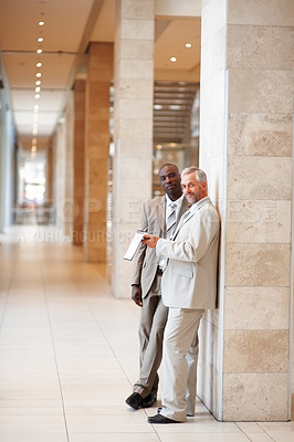 Buy stock photo Portrait of two business colleagues standing together in the hallway