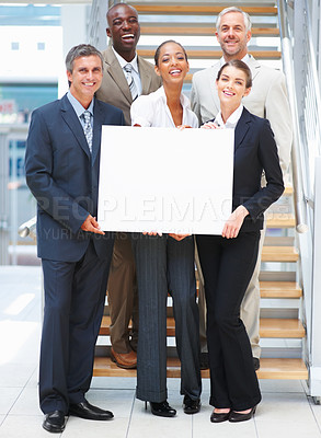 Buy stock photo Business woman holding an empty bill board with her colleagues on the stairs