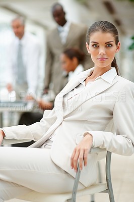 Buy stock photo Portrait of a beautiful young business woman sitting with colleagues at the background