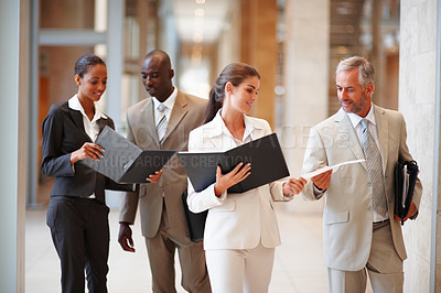 Buy stock photo Group of business colleagues holding a file at the hallway