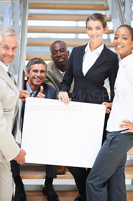 Buy stock photo Business people holding an empty bill board and smiling confidently
