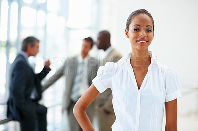 Buy stock photo Image of an ambitious African American business woman posing with colleagues at the back