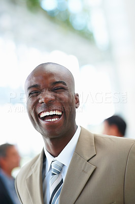 Buy stock photo A creative business man laughing with people at the background