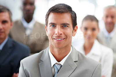 Buy stock photo Confident handsome business man with colleagues at the back