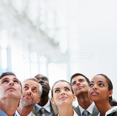 Buy stock photo A team of happy business people looking upwards at copyspace