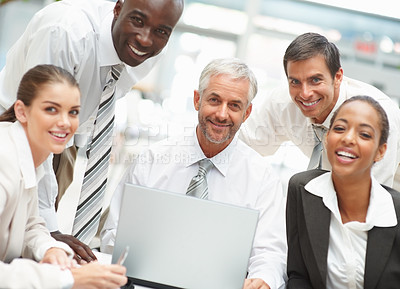 Buy stock photo Portrait of a group of successful business people working together on a laptop