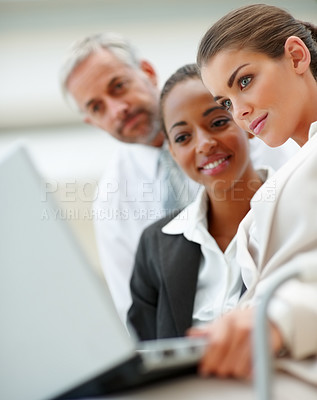 Buy stock photo Team of business colleagues working on a laptop