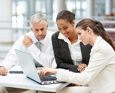 Buy stock photo Young women and a mature business man working on a laptop
