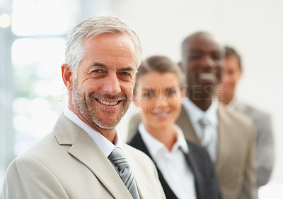Buy stock photo Portrait of a successful business leader with his team standing behind him