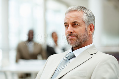 Buy stock photo A contemplative business man with people in the background
