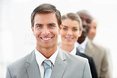 Buy stock photo Portrait of a young handsome business man standing in a line with his colleagues
