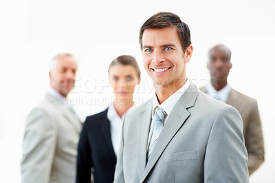 Buy stock photo Portrait of a confident young business man with his colleagues standing at the back