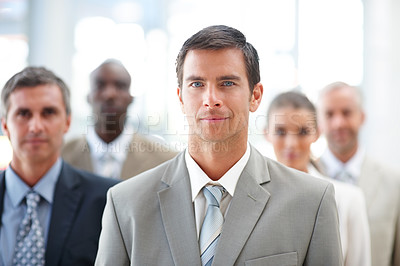 Buy stock photo Portrait of a handsome business man with colleagues at the background