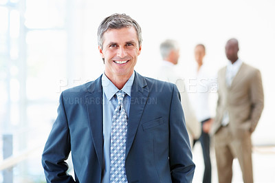 Buy stock photo A handsome confident professor smiling with people standing at the background