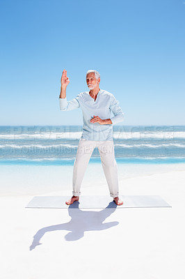 Buy stock photo Portrait of an elderly man practicing martial arts on the beach