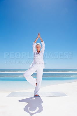 Buy stock photo Full length image of a senior old woman practicing yoga at the beach