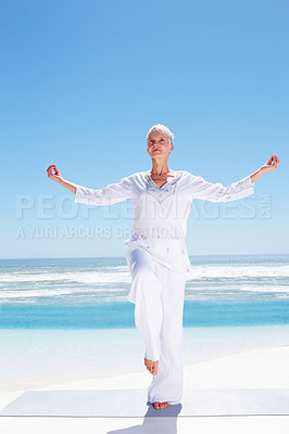 Buy stock photo Full length image of an elderly woman practicing yoga at the beach