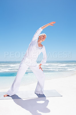 Buy stock photo Full length image of a mature old woman practicing yoga at the beach