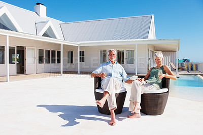 Buy stock photo Happy senior couple enjoying themselves outdoors with their house at the back