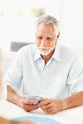 Buy stock photo Portrait of a senior man playing a game of cards