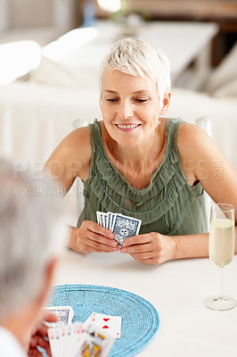 Buy stock photo Portrait of an old woman playing a game of cards with a man