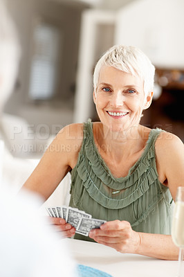 Buy stock photo Portrait of a happy mature woman playing a game of cards