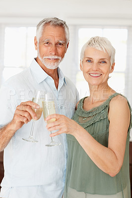 Buy stock photo Portrait of an elderly couple celebrating with a glass of champagne