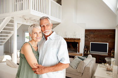 Buy stock photo Happy mature couple embracing eachother in their stylish home while gazing out of frame - copyspace