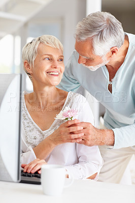 Buy stock photo Portrait of an old man giving flower to wife while she's working on computer